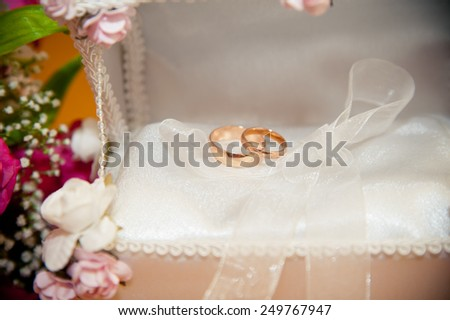 two wedding rings lie in the trunk for rings next to a bouquet of the bride - stock photo