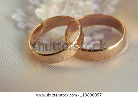 Two wedding rings lie on a white pillow - stock photo