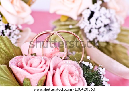 Two wedding rings macro on an artificial bouquet - stock photo