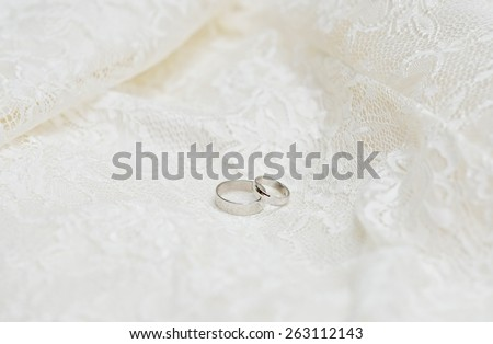Two wedding rings on a white lace background  - stock photo