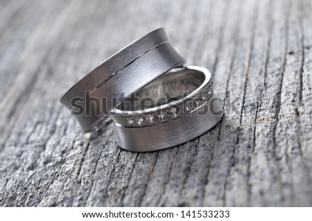 two wedding rings on wooden surface - stock photo