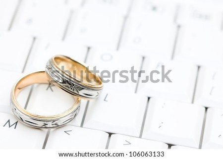 Two Wedding rings sitting on a white computer keyboard - stock photo