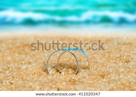 Two wedding silver rings  in the sand on the background of beach and sea - stock photo
