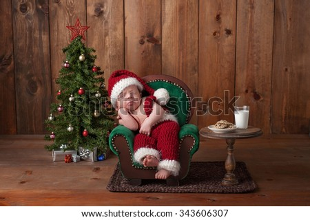 Two week old, newborn, baby boy wearing a crocheted Santa suit. He is sleeping on a tiny armchair. Shot in the studio with props, including a Christmas tree, glass of milk and crocheted cookies.  - stock photo