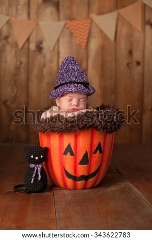 Two week old newborn baby girl wearing a witch costume. She is sleeping in a Jack-O-Lantern. Shot in the studio with a rustic wood background. - stock photo