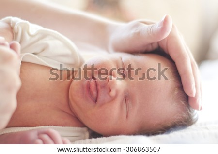 Two weeks old baby lying on the bed - stock photo