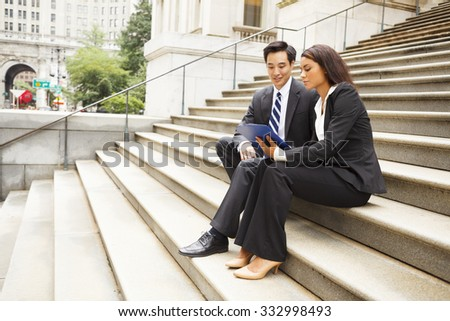 Two well dressed professionals working together outdoors. Woman shows man something on a clipboard Could be lawyers, business people etc. - stock photo