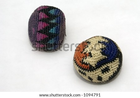 Two well-worn hacky-sack footbags against a white background. - stock photo