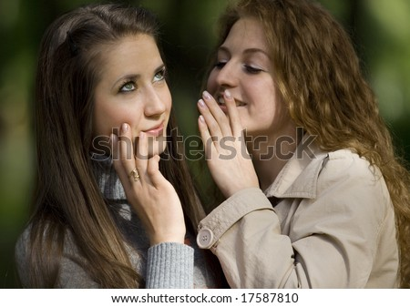 two whispering girlfriends - stock photo