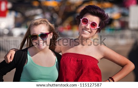 Two white and Hispanic best friends at an amusement park - stock photo