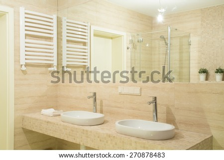 Two white basins in new big bathroom with granitic tiles - stock photo