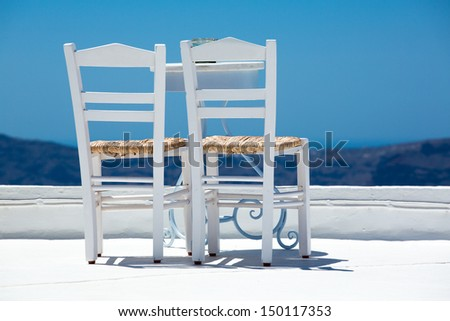 Two white chairs and a blurred panoramic view of the hills of santorini, Greece 2013. - stock photo