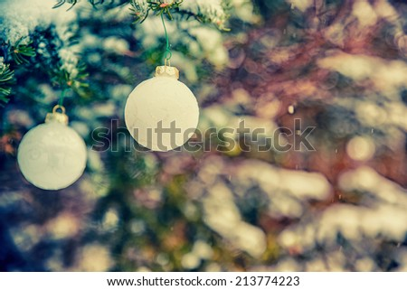 Two white Christmas bauble decorations hanging off a spruce tree outside partially covered in snow.  Room for copy space.  Filtered for a retro vintage look.  - stock photo