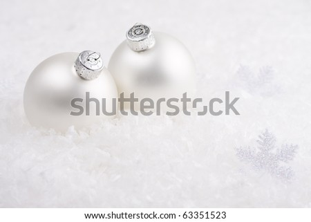 Two white Christmas baubles in the snow. - stock photo