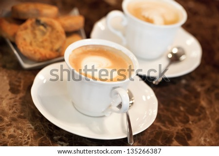 Two white cups of Cappuccino coffee with heart shaped milk foam. Selective focus - stock photo