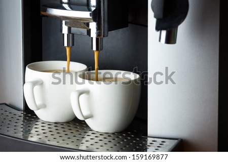 Two white cups of espresso in coffee machine - stock photo