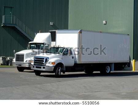 Two White Delivery Trucks Backed Up to A Warehouse Building - stock photo