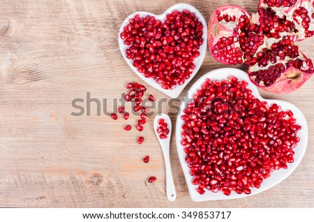 Two white heart shaped plates full of fresh ripe juicy pomegranate seeds, little spoon, whole fruit and ripe one on wooden background. - stock photo