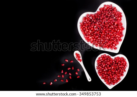 Two white heart shaped plates full of fresh ripe juicy pomegranate seeds, little spoon, whole fruit and ripe one on black background. - stock photo