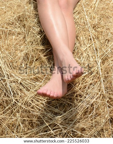Two white legs of a Caucasian teenage girl sitting on hay bales in summertime. - stock photo