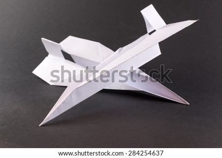Two white paper airplanes crashing in flight on a black background - stock photo