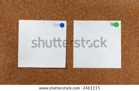 Two white pieces of paper pinned to a corkboard. - stock photo