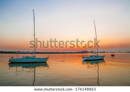 Two white sailboats in twilight time - stock photo