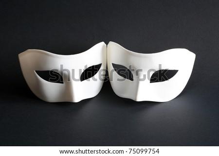 Two white venetian masks on dark background - stock photo