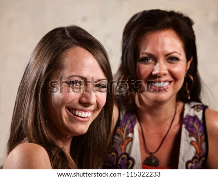 Two white women smiling and laughing together - stock photo