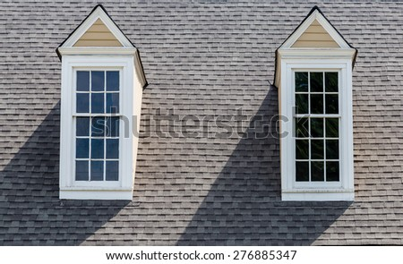Two white wood dormers on a grey asphalt roof - stock photo