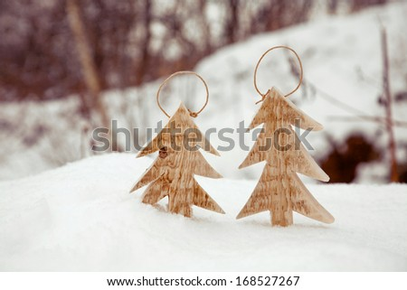 Two white wooden handmade trees on the snow. Christmas decoration. - stock photo