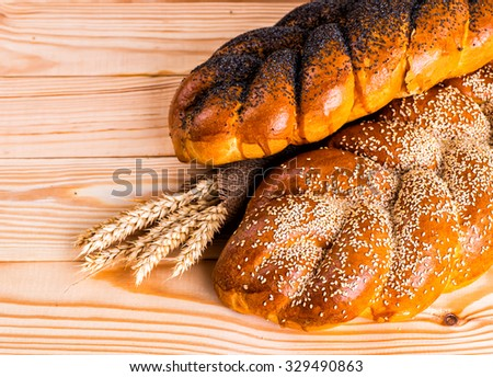 Two whole fresh challah bread with poppy and sesame on a wooden background - stock photo