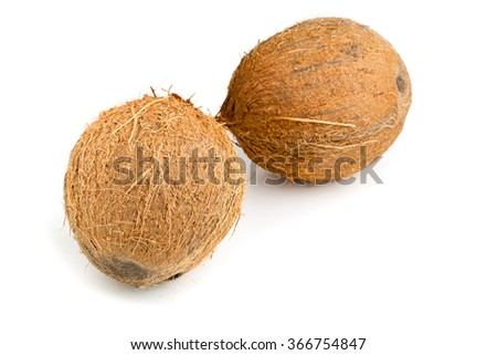 Two whole uncut coconuts over white background - stock photo