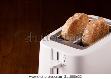 Two whole wheat bread and white toaster on wooden table. - stock photo