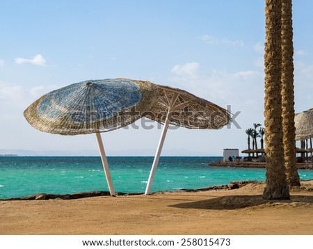 Two wicker beach umbrellas on a tropical beach. Egyptian resort with a blue lagoon and palms on the tropical beach of Red Sea.  - stock photo