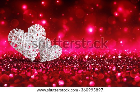 Two Wicker Hearts On Red Sparkle Glitter  - stock photo