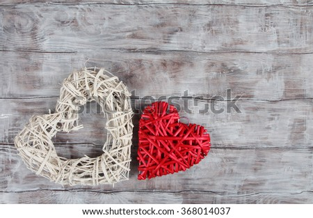 Two wicker Valentine Day hearts on wooden background - stock photo