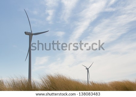 Two wind turbines against a blue sky towering over the grass covered dunes. - stock photo
