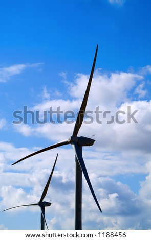 Two wind turbines against fluffy clouds - stock photo