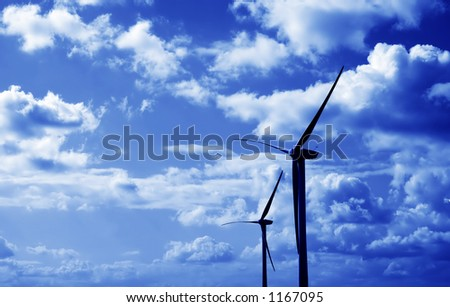 Two wind turbines against fluffy clouds, blue tint over. - stock photo