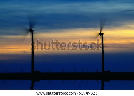 two wind-turbines at seacoast in sunset - stock photo
