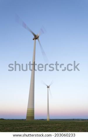 Two wind turbines, blue sky, motion blur. Location: Rhineland, Germany - stock photo