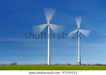 Two wind turbines in movement against blue sky - stock photo