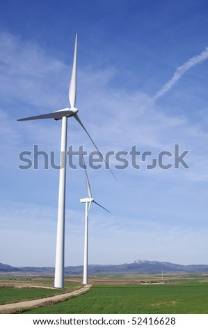 two windmills in a field with blue sky - stock photo