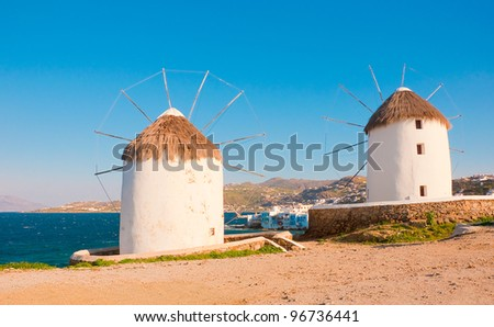 Two windmills of Mykonos on the background of Little Venice. White buildings, blue sky and the sea - the national colors of Greece - stock photo