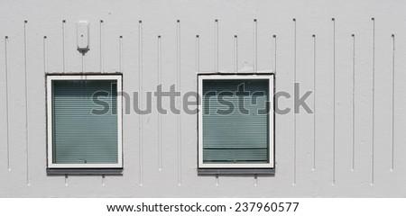 Two windows in a gray concrete facade - stock photo