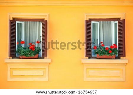 two windows on orange vivid wall with geraniums, romania style - stock photo