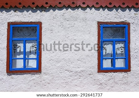 Two windows on the white wall of an old traditional peasant house - stock photo
