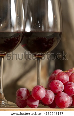 Two wine cups, grapes and fire on the background. - stock photo