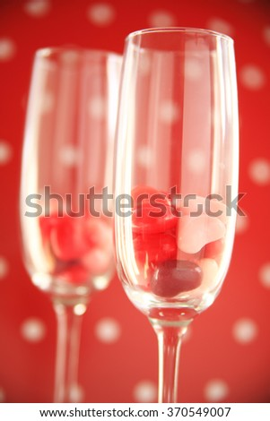 Two wine flutes with candy hearts against a red and white polka dot background - stock photo